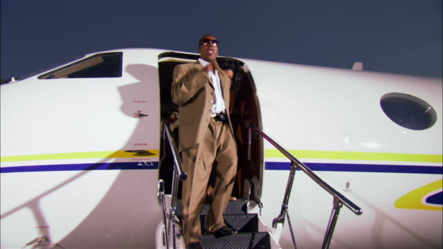 medium shot businessman and diva exiting private airplane and running across tarmac / long beach, california, usa - steps and staircases stock videos & royalty-free footage