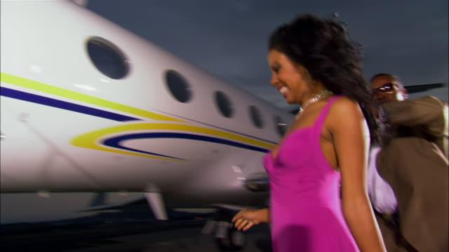 medium shot businessman and diva running across tarmac and entering private airplane / long beach, california, usa - eitelkeit stock-videos und b-roll-filmmaterial