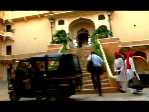 vídeos de stock, filmes e b-roll de medium shot businessman arriving at hotel in taxi and walking up stairs / bellman bowing to him - adereço de cabeça