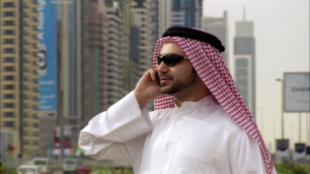 medium shot businessman in middle eastern attire talking on cellular phone, skyscrapers and busy street in background - westernisation stock videos & royalty-free footage