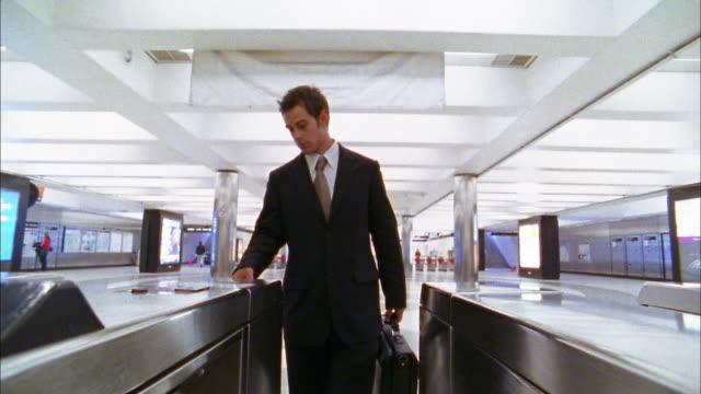 Medium shot businessman inserting and removing transit card into subway turnstile