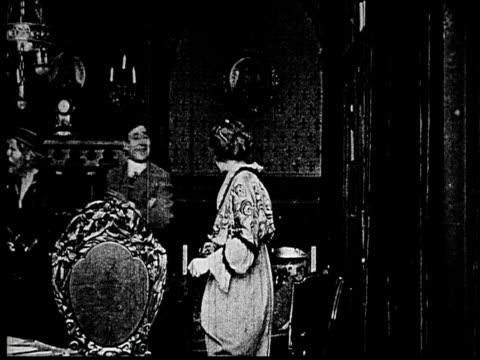 stockvideo's en b-roll-footage met 1914 b/w medium shot businessman introducing elderly sailor to scared woman  - compleet pak
