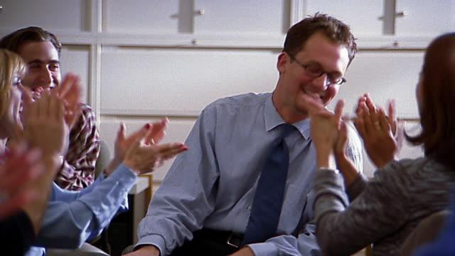 Medium shot businessman is applauded by his coworkers