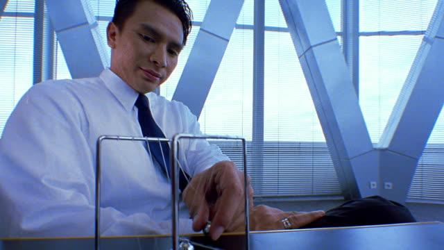 stockvideo's en b-roll-footage met medium shot businessman sitting at desk and hitting balls on newton's cradle desk toy - slinger van newton
