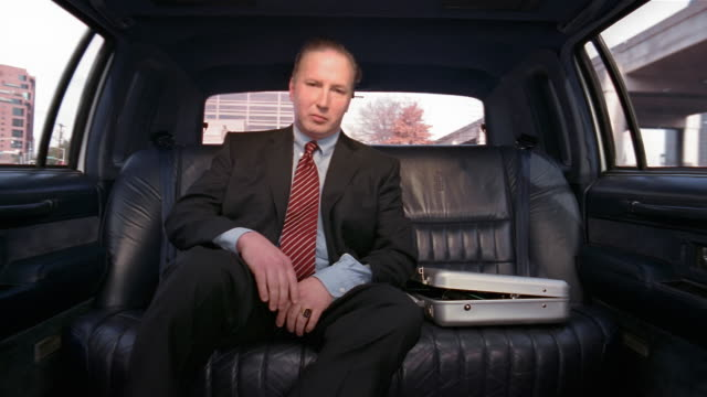 Medium shot businessman sitting forward in limo looking at camera and smiling slightly