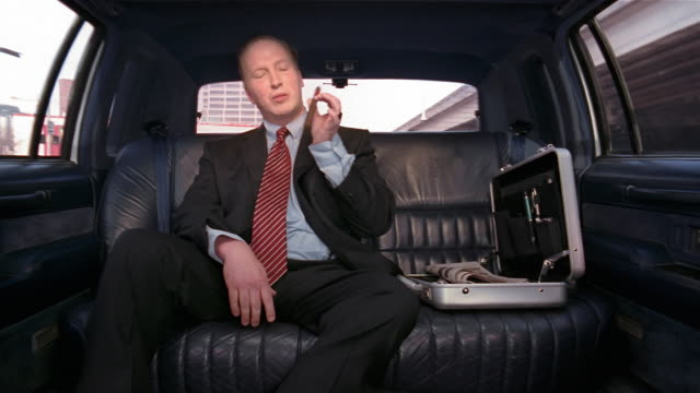 Medium shot businessman sitting in limo chomping on cigar and pretending to smoke