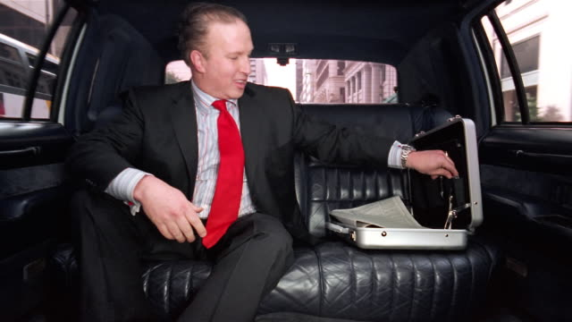 medium shot businessman sitting in limo reading newspaper / smiling and looking smug / talking on cell phone and laughing - passenger stock videos & royalty-free footage