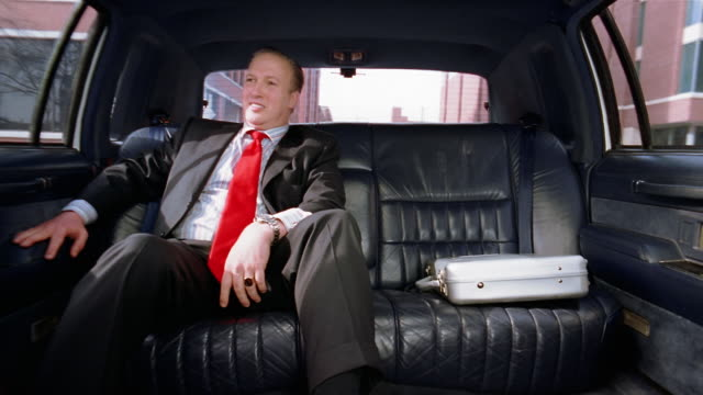 Medium shot businessman sitting in limo / smiling and looking smug