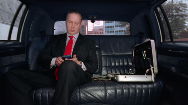medium shot businessman sitting in limo using pda / looking out window - electronic organiser stock videos & royalty-free footage