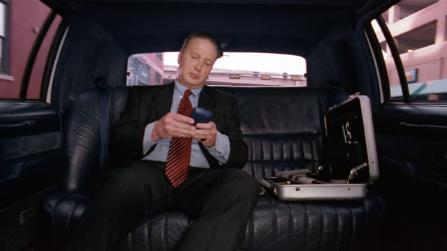 Medium shot businessman sitting in limo using pda / putting device away in briefcase and closing case / looking out window
