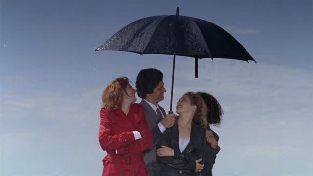 vidéos et rushes de medium shot businessman smiling and sheltering women from rain with umbrella - vêtement de pluie