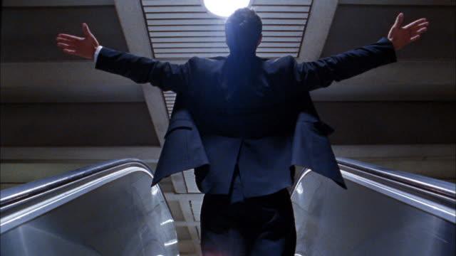medium shot businessman stretching arms on escalator - fare lo stretching video stock e b–roll