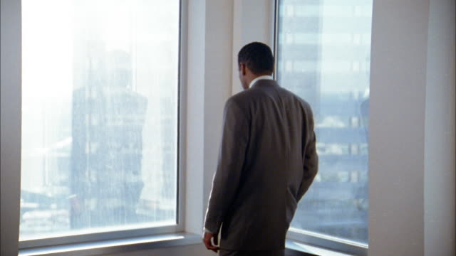 Medium shot businessman talking on cell phone and looking out window