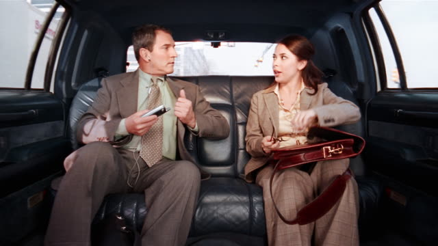 medium shot businessman using pda and businesswoman talking on cell phone in limo / woman pulling out papers for man to sign / shaking hands - tie stock videos and b-roll footage