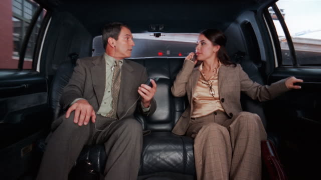 Medium shot businessman using pda and businesswoman talking on cell phone in limo / talking to one another