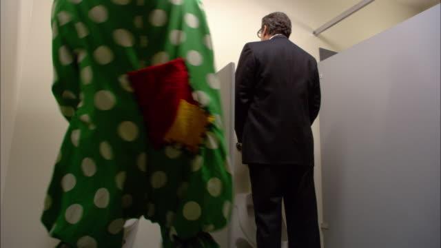 medium shot businessman using urinal / clown entering and using urinal / businessman laughing at clown / low angle - urinal stock videos & royalty-free footage
