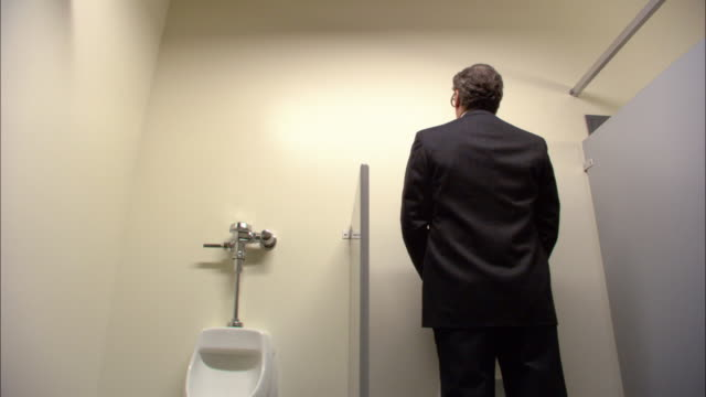 medium shot businessman using urinal / los angeles - 小便器点の映像素材/bロール