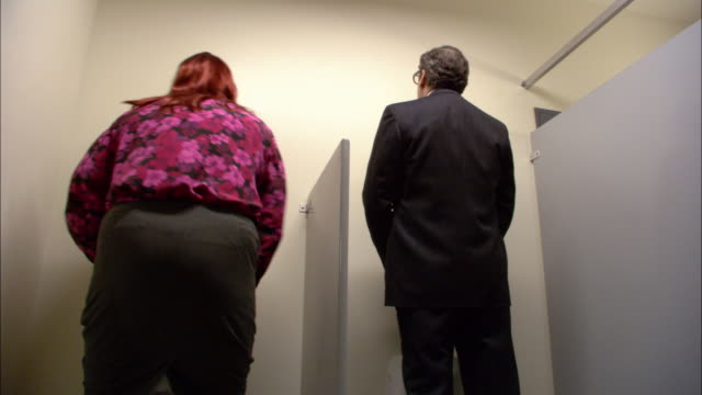 medium shot businessman using urinal / transvestite entering and using urinal / exchanging glances / low angle - privacy stock videos & royalty-free footage