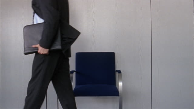 Medium shot businessman waiting in chair outside office / getting up