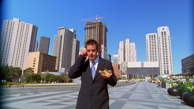 Medium shot businessman walking across plaza eating pizza and talking on cellular phone