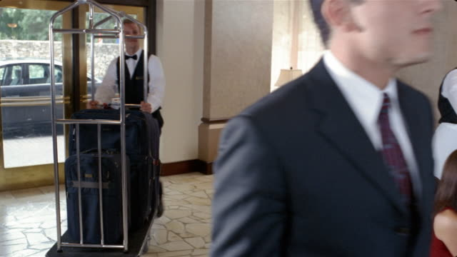 Medium shot businessman walking through hotel lobby followed by bellhop with luggage cart / passing by waitress serving women coffee