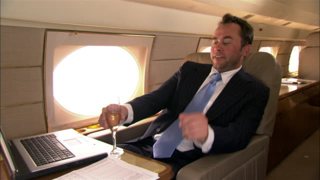 medium shot businessman with laptop reclining seat and drinking champagne in private airplane - zurücklehnen stock-videos und b-roll-filmmaterial