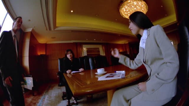 Medium shot businessmen and Asian businesswomen talking in conference room