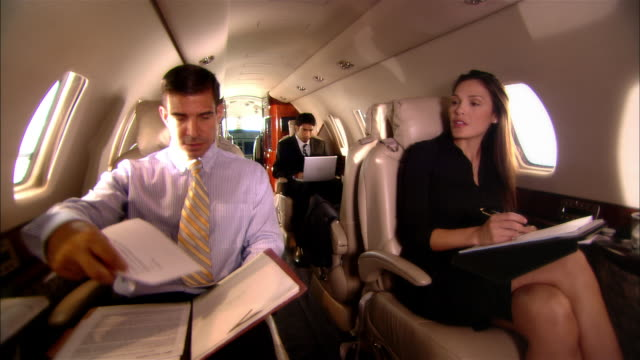 medium shot businessmen and businesswoman reading documents and text messaging in private jet/ miami, florida, usa - gambe accavallate video stock e b–roll
