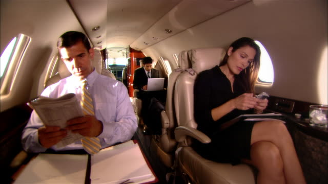 vídeos de stock e filmes b-roll de medium shot businessmen and businesswoman reading documents and text messaging in private jet/ miami, florida, usa - cabine de passageiros