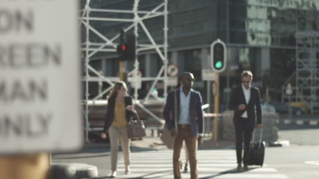 medium shot, businesspeople cross street - verkehrs leuchtsignal stock-videos und b-roll-filmmaterial
