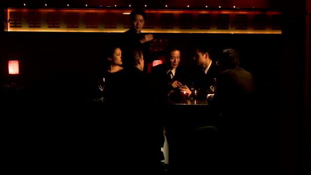 medium shot businesspeople having meeting in restaurant as waiter serves drinks - asian and pacific islander stock videos & royalty-free footage