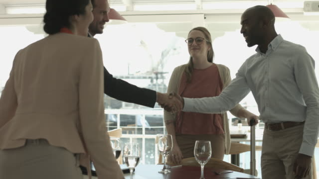 vídeos de stock, filmes e b-roll de medium shot, businesspeople meet and greet at restaurant - desaparecer gradualmente