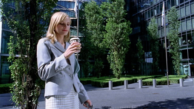Medium shot businesswoman drinking coffee / text messaging with mobile phone / Berlin