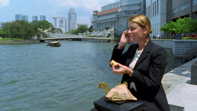 medium shot businesswoman eating lunch and  answering, then talking on cell phone on riverbank / boat in background - packed lunch stock videos and b-roll footage