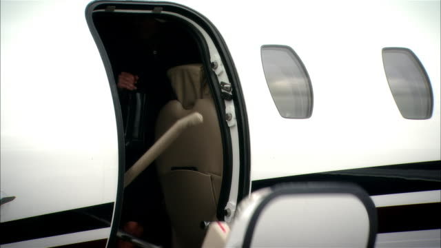 medium shot businesswoman exiting private jet and signing documents for colleagues then enters chauffeur-driven luxury car at opa locka airport/ miami, florida, usa - スウィッシュパン点の映像素材/bロール