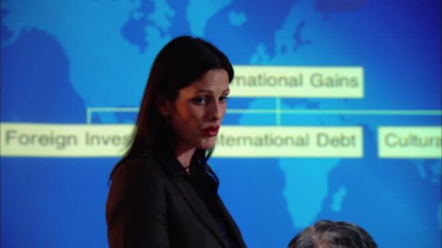 medium shot businesswoman giving presentation in board room/ new york, new york - strategia di vendita video stock e b–roll