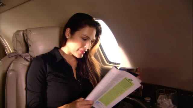 vídeos de stock, filmes e b-roll de medium shot businesswoman reading magazine in private jet/ miami, florida, usa - revista publicação