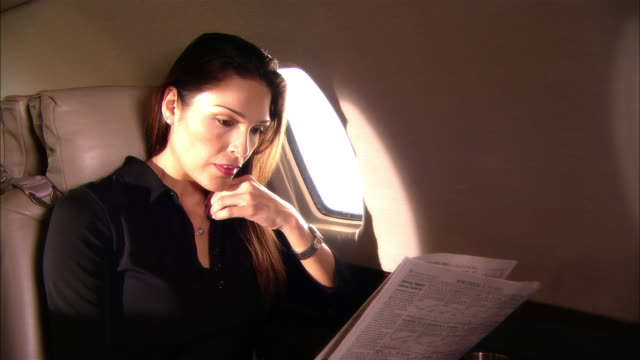 Medium shot Businesswoman reading newspaper in private jet/ Miami, Florida, USA