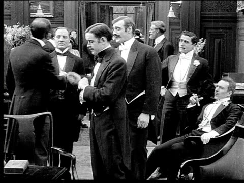 1914 b/w medium shot butler serving wealthy men drinks at party - party social event stock videos & royalty-free footage