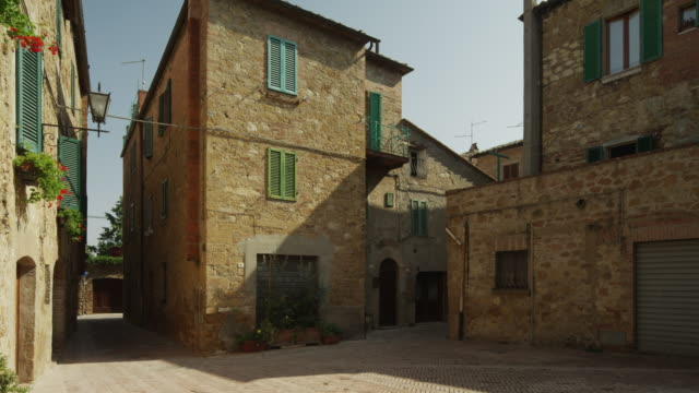 Medium shot, camera pans right across Italian courtyard / Piensa, Tuscany, Italy