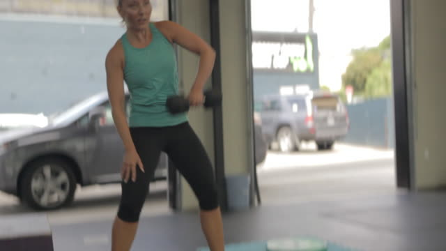 medium shot. camera tilts and follows as carly performs series of dumbell snatches. - dumbbell stock videos & royalty-free footage