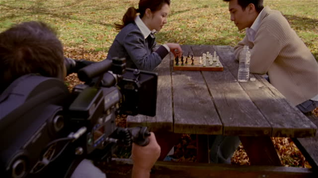 Medium shot cameraman filming young Asian couple playing chess in park/ Solebury, Pennsylvania