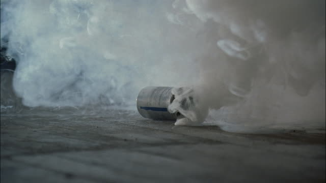 medium shot canister of tear gas rolling and emitting smoke / smoke stopping - tear gas stock videos & royalty-free footage