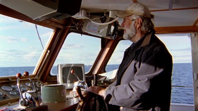 vidéos et rushes de medium shot captain of boat standing at the wheel and steering - capitaine de bateau