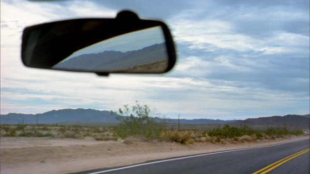 medium shot car driving on desert road / hand adjusting rear view mirror - rear view mirror stock videos and b-roll footage