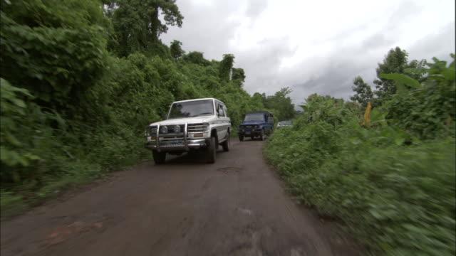medium shot pov - car driving towards camera down country road / bangladesh  - 4x4 stock videos & royalty-free footage