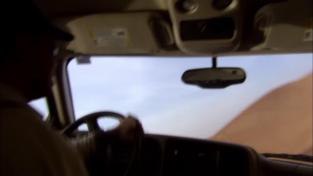 medium shot car interior man driving 4x4 suv across sand dunes in desert - baseballmütze stock-videos und b-roll-filmmaterial