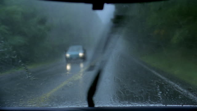 medium shot car point of view driving along rainy highway / windshield wipers wiping away rain - rain stock videos & royalty-free footage