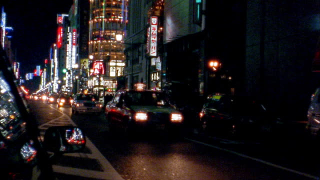 Medium shot car point of view driving on boulevard at night / Tokyo