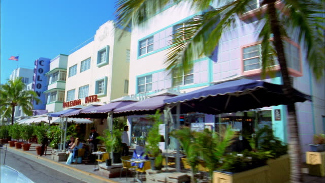 medium shot car point of view passing restaurant awnings, cafes and palm trees / miami beach, florida - マイアミ点の映像素材/bロール